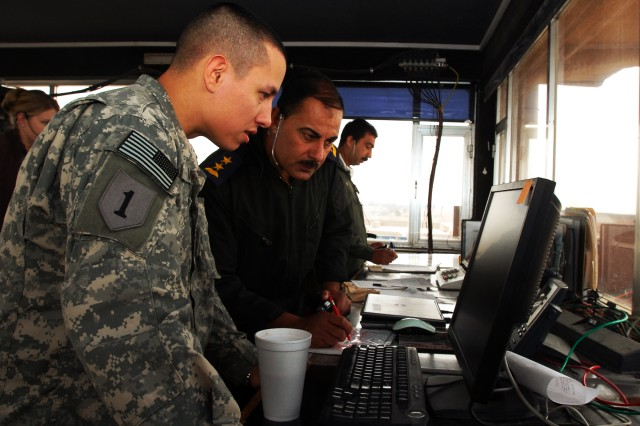 Sgt. Douglas Miller, an air traffic controller serving in Iraq with the Enhanced Combat Aviation Brigade, 1st Infantry Division, mans the control tower on Camp Taji with a controller from the Iraqi army. The tower is manned 24-hours a day by controllers from the brigade, the Iraqi army, and contractors from the Washington Consulting Group. (U.S. Army photo by Spc. Roland Hale, eCAB, 1st Inf. Div. PAO)