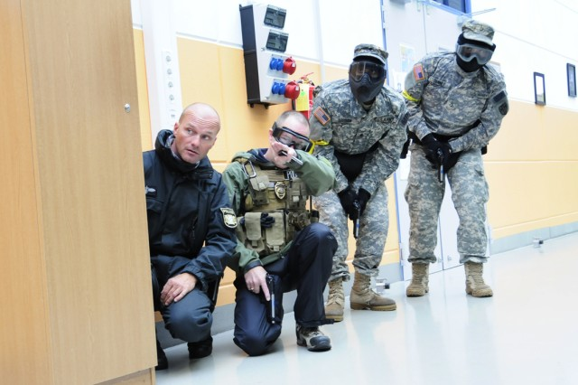 GRAFENWOEHR, Germany - Garrison and host nation law enforcement officials provide cover in Rose Barracks\' Building 134 during Charging Boar 2010, an anti-terrorism force protection exercise, Sept