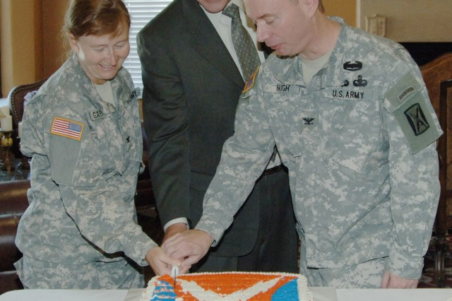 Col. Mary Garr, 502nd Mission Support Group commander; Hal Marsh, Network Enterprise Center director; and Col. Chris Haigh, 106th Signal Brigade commander, cut the cake after a transfer of authority ceremony Oct. 11 at Lincoln Military Housing Community Center.