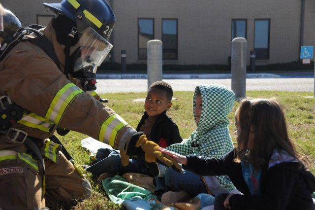 Barry Shiver, Fort Rucker civilian firefighter, shows children at the Child Development Center how the firefighter suit works Oct. 6. Fire Prevention Week ran from Oct. 3-9 and the Fire Prevention Office staff hosted several on-post events to educate children and adults on what to do in case of a fire emergency.