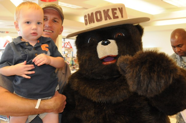 Joshua Blanton, 1, and his father, Capt. Jesse Blanton, pose with Smokey the Bear at the Post Exchange, Oct. 9. Smokey visited the PX during Fire Prevention Week, Oct. 3-9 to help children learn more about fire safety. For more photos, visit the Army Flier Facebook page.