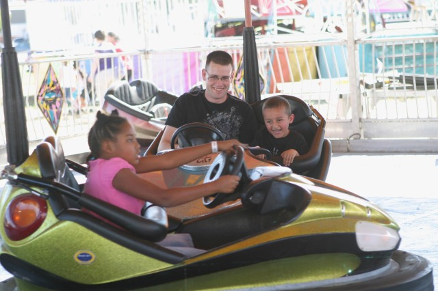 Spc. Gerald Corbett, Company B, 1st Bn., 28th Inf. Regt., 4th HBCT, 1st Inf. Div., and his son, Chris, a Custer Hill Elementary School kindergartener, ride the bumper cars during Fort Riley's Oktoberfest Oct. 8 at Rally Point Field.