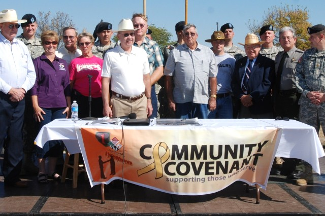 Morris County community leaders, along with Soldiers and leaders from the 1st HBCT, 1st Inf. Div. and Fort Riley stand behind the Army Community Covenant following the signing of the covenant during a ceremony Oct. 9 at Canning Creek Cove near Council Grove, Kan.