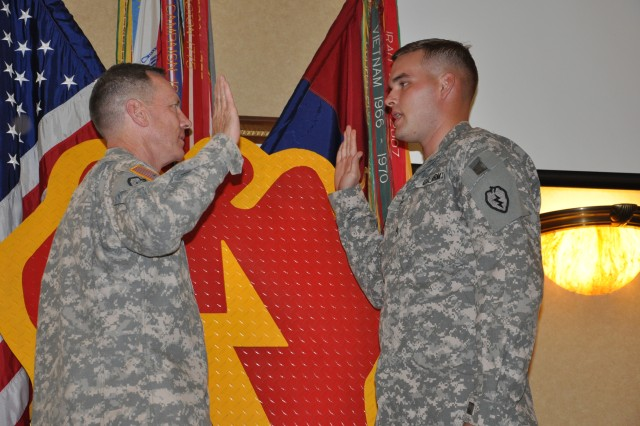 "Staff Sgt. Lawrence Daniel Henry, 25th Infantry Division Band, reenlists during the 25th Infantry Division Commanding General's Retention Celebration held at the Nehelani Club, Schofield Barracks, Hawaii, Oct. 13. ""I want to thank this community, leadership of this division, and the units that allow the Soldiers to see the merit in their service,"" said Maj. Gen Bernard S. Champoux, commanding general, 25th Inf. Div. during his speech at the ceremony."
