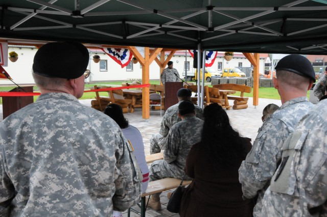 Attendees gather with officials to officially open the pavilion at U.S. Army Garrison Grafenwoehr's USO, Sept. 28. The pavilion features an outdoor theater system, two smokers and grills, handcrafted log picnic tables and free Wi-Fi.