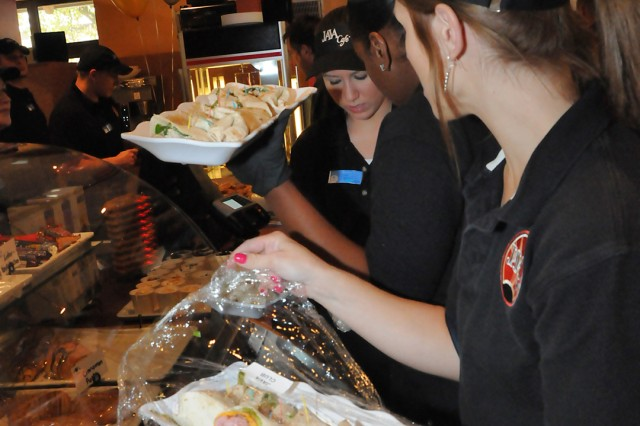 Employees of the new Grafenwoehr Java Cafe prepare to hand out samples of the cafe's new Signature Sandwich wraps, Sept. 30. The cafe, which is inside the bowling alley opens at 7 a.m.