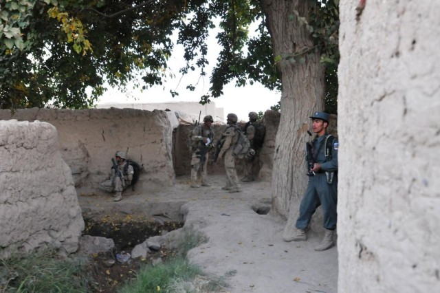 Canadian soldiers talk to one another before elements of the Afghan National Army, Afghan National Police and Canadian soldiers conduct a cordon search mission on a compound. Canadian elements of the 1st Battalion, The Royal Canadian Regiment, ANA and ANP conduct partnered dismounted patrols, and cordon and search missions on a regular basis around the Panjwai'i District in Kandahar province. Ultimately, the priority for ISAF (International Security Assistance Forces) is to build up the ANA, and ANP, and hand over security to the Afghan forces.