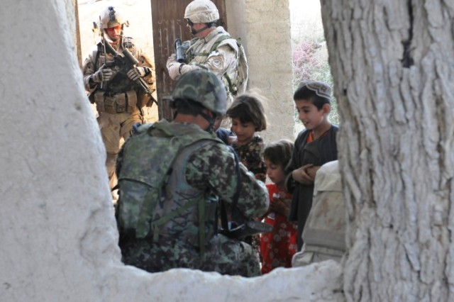 Afghan children talk to an Afghan soldier before elements of the Afghan National Army, Afghan National Police and Canadian Soldiers conduct a cordon search mission. Canadian elements of the 1st Battalion, The Royal Canadian Regiment, ANA and ANP conduct partnered dismounted patrols and cordon and search missions on a regular basis around the Panjwai'i District in Kandahar province. Ultimately, the priority of ISAF (International Security Assistance Forces) is to build up the ANA, and ANP, and hand over security to the Afghan forces.