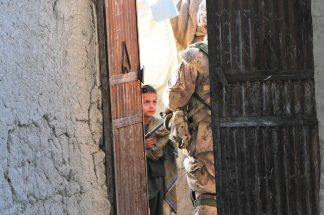 An Afghan child looks at a Canadian Soldier as Afghan National Army soldiers and Canadian elements of the 1st Battalion, The Royal Canadian Regiment conduct a cordon search mission. ANA and Afghan National Police conduct partnered dismounted patrols and cordon and search missions on a regular basis around the Panjwai'i District in Kandahar province. Ultimately, the priority for ISAF (International Security Assistance Forces) is to build up the ANA, and ANP, and hand over security to the Afghan forces.