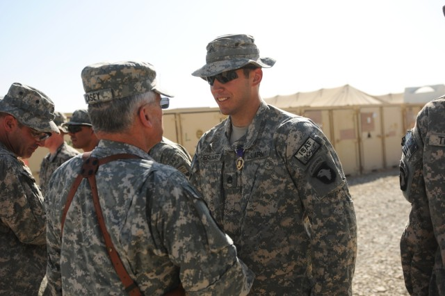 FORWARD OPERATING BASE HOWZ-E-MADAD, KANDAHAR, AFGHANISTAN – Gen. George W. Casey, the Army Chief of Staff, shakes hands with Staff Sgt. Joseph Perminas, a 32 year old native of Antiock, Il. with Company A, 1st Battalion, 502nd Infantry Regiment, 2nd Brigade Combat Team, 101st Airborne Division (Air Assault), during an awards ceremony at Forward Operating Base Wilson, Kandahar province, Afghanistan, Oct.12 . Casey pinned Perminas with a Purple Heart for shrapnel wounds he received to his lower back when a hand grenade exploded in Zharay, Oct. 2.