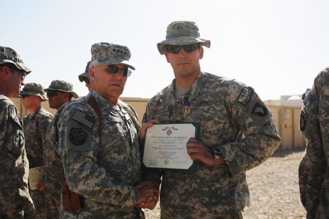 FORWARD OPERATING BASE HOWZ-E-MADAD, KANDAHAR, AFGHANISTAN – Gen. George W. Casey, the Army Chief of Staff, holds a certificate with Staff Sgt. Joseph Perminas, a 32 year old native of Antiock, Illinois, with Company A, 1st Battalion, 502nd Infantry Regiment, 2nd Brigade Combat Team, 101st Airborne Division (Air Assault), during an awards ceremony at Forward Operating Base Wilson, Kandahar province, Afghanistan, Oct.12 . Casey pinned Perminas with a Purple Heart for shrapnel wounds he received to his lower back from a hand grenade explosion in Zharay, Oct. 2.