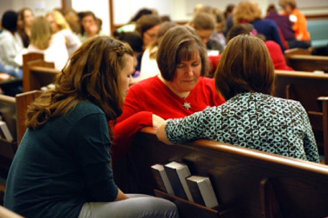 Beth Witte, Rose McConnell and Nicole Dabkowski pray at the conclusion of the Protestant Women of the Chapel meeting Oct. 12 in the new Frontier Chapel's Worship Center.