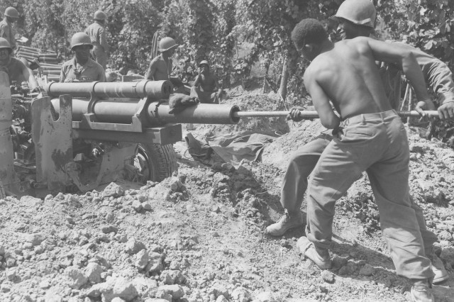 "The gun crew of Battery ""B,"" 598th Field Artillery, 92nd Infantry Division, readies their 105 howitzer before receiving a fire mission on September 1, 1944 near the Arno River in Italy.  (Edward M. Almond Collection)"