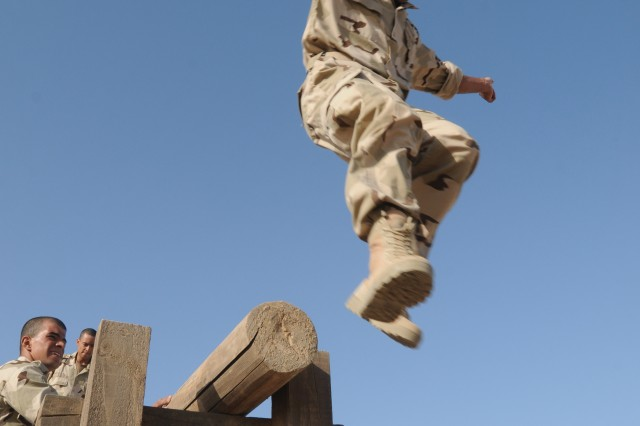 An Iraqi Army jundi jumps off a confidence course obstacle as part of an IA Basic Combat Training course at the Besmaya Combat Training Center Oct. 10. The Bomb Disposal School at BCTC is hosting the course and providing resources to meet a surge of new Iraqi Army recruits.