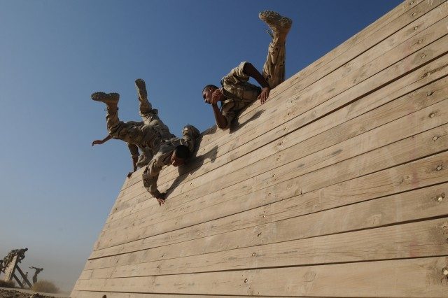 Iraqi Army jundis flip over a confidence course wall as part of their Basic Combat Training course at the Besmaya Combat Training Center Oct. 10. The BCTC is hosting the Basic Combat Training course due to a recent influx of new Iraqi Army recruits.