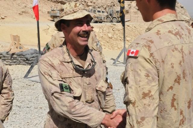 FORWARD OPERATING BASE MA'SUM GHAR, Afghanistan - Regimental Sergeant Major, Chief Warrant Officer Mike R. Hornbrook, shakes hands with a Canadian soldier. Hornbrook and Honorary Colonel of the Regiment retired Major General Walter M. Holmes were invited to pin the medals on soldiers of the 1st Battalion, The Royal Canadian Regiment and other elements of the Battle Group, Oct. 7 during a medals parade ceremony
