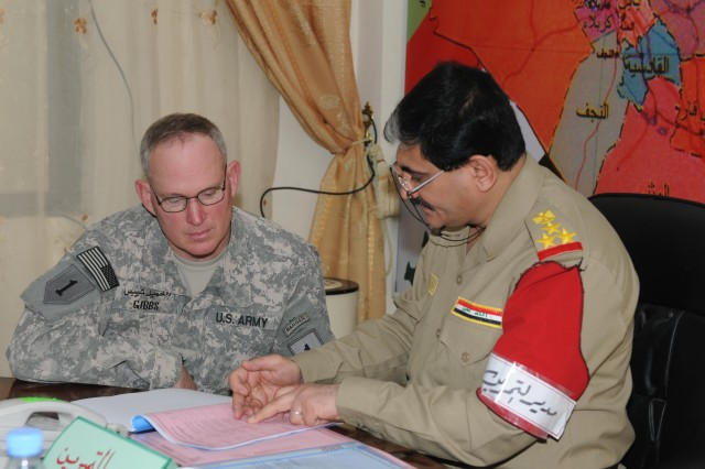 Brig. Gen. Ricky Gibbs, United States Division-South deputy commanding general of maneuver, and Staff Brig. Gen. Dhafar Nathmy Jamil, the 4th Region DBE commander talk about the map exercise at the 4th Region Department of Enforcement Headquarters in Basra, Iraq, Oct. 5 moments after it finished. The exercise was the first joint exercise between the Department of Border Enforcement and Iraqi Army at the region level.