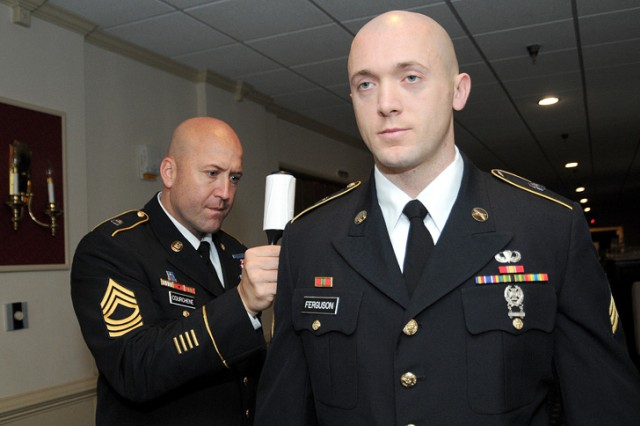 """Master Sgt. Shane Courchene uses a lint roll to tidy up the uniform of Sgt. John Ferguson.  Ferguson was minutes away from facing a board of sergeants major assembled for the board appearance event of the 2010 Department of the Army Noncommissioned Officer and Soldier of the Year """"Best Warrior"""" Competition.  Best Warrior annually tests the physical and mental capacities of 24 Soldiers and NCOs in a competition that features Warrior Tasks and Battle Drills and the Army Physical Fitness Test.  It is being held Oct. 17-22 at Fort Lee, Va."""