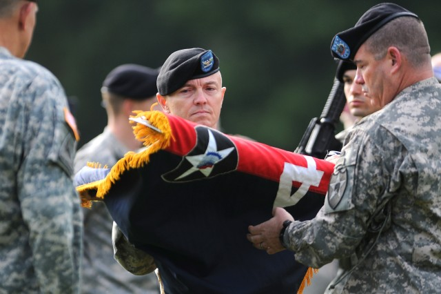 Col. John Norris, center, and Command Sgt. Maj. Jeff Huggins, right, uncase the 4th Bde., 2nd Inf. Div. colors during a ceremony Oct. 7.