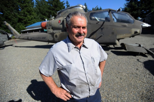 """Tom Wojnar, a Washington State Department of Natural Resources helicopter mechanic and Army Vietnam War veteran, stands in front of the AH-1G Cobra helicopter Oct. 6 where it is held at a DNR property in Tumwater. The """"Virginia Rose II"""" flew into the history books on Sept. 4, 1967 as the first AH-1G to fly in Vietnam."""