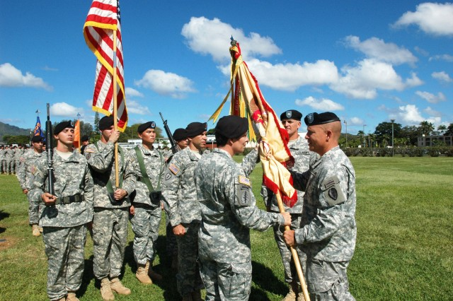 "Lieutenant Col. Keriem Kvalevog (left center), incoming commander, 209th Aviation Support Battalion, 25th Combat Aviation Brigade (CAB), accepts the battalion Colors from Col. Mike Lundy, commander, 25th CAB, during the ""Lobos"" Battalion's change of command on Sills Field at Schofield Barracks, Oct. 15. Kvalevog assumed command from Lt. Col. Ramsey Bentley II during the ceremony."