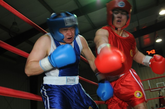Air Force Capt. Joey Ingram (left), an intelligence, survey and reconnaissance officer with the 24th Intelligence Squadron, liaison officer to the 1st Armored Division, USD - C, and a Chattanooga, Tenn., native, cringes Oct. 9 after his opponent, Spc. Andrew Blaize lands a punch during the Boxing Smoker 2, a boxing competition hosted by Division Special Troops Battalion, 1st Armd. Div., USD-C, at Camp Liberty, Iraq. Capt. Ingram won the bout.