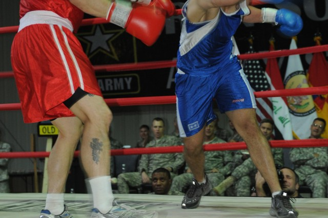 Spc. Henry Ruiz (right), punches his opponent, Staff Sgt. Chris Kennebeck, Oct. 9 during their bout in the Boxing Smoker 2, an event hosted by Division Special Troops Battalion, 1st Armored Division, United States Division - Center, at Camp Liberty, Iraq.