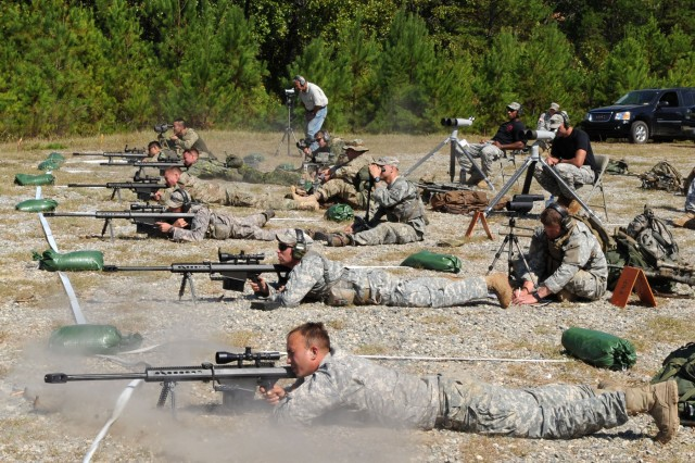 Snipers fire 50-caliber rifles at vehicle targets while spotters watch for hits through magnified optical devices.