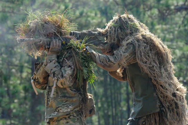During competitive shooting at the 10th Annual International Sniper Competition at Fort Benning, Ga., two snipers wearing Ghillie suits combine to form an over-the-shoulder supported firing position. A ghillie suit is a type of camouflage worn by snipers made from cloth or fibers, with the name originating from the Gaelic word for servant, gille.