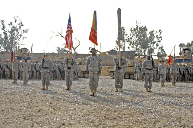 CONTINGENCY OPERATING SITE MAREZ, Iraq - Command Sgt Maj. Calvin Coler (center), with 5th Battalion, 82nd Field Artillery Regiment, 4th Advise and Assist Brigade, 1st Cavalry Division, stands before the battalion's recently uncased colors during the unit's transfer of authority ceremony, Oct. 12.