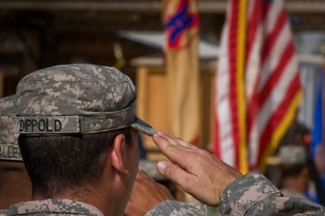 """Soldiers salute the American flag during the National Anthem at the Joint Sustainment Command-Afghanistan transfer of authority ceremony Oct. 17 at Kandahar Airfield, Afghanistan."""""""