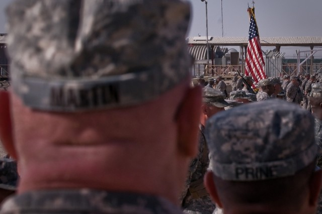 """Soldiers watch as the color guard brings the American Flag to the front of the formation during the Joint Sustainment Command-Afghanistan transfer of authority ceremony Oct. 17 at Kandahar Airfield, Afghanistan."""""""