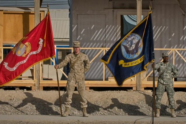 """Servicemembers hold flags representing the Army, Marine Corps, Navy, and Air Force during the Joint Sustainment Command-Afghanistan transfer of authority ceremony Oct. 17 at Kandahar Airfield, Afghanistan."""""""
