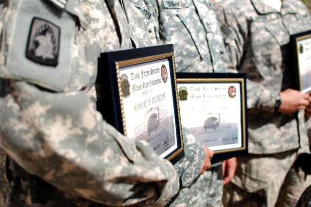 Soldiers serving in Iraq with the 3rd Battalion, 158th Aviation Regiment hold certificates of re-enlistment. The battalion held a ceremony Oct. 19, re-enlisting 15 troops at once. (U.S. Army photo by Spc. Roland Hale, eCAB, 1st Inf. Div. PAO)