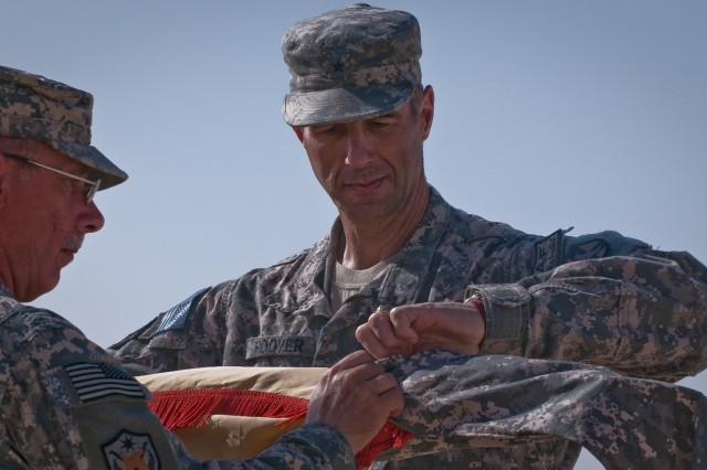 """Brig. Gen. Reynold Hoover, outgoing commander of Joint Support Command Aca,!"""" Afghanistan, cases his unitAca,!a,,cs colors during the JSC-A transfer of authority ceremony Oct. 17 at Kandahar Airfield, Afghanistan."""