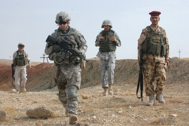 CONTINGENCY OPERATING SITE MAREZ, Iraq - Lt. Jeremiah Yaden (left), a platoon leader of with 1st Squadron, 9th Cavalry Regiment, 4th Advise and Assist Brigade, 1st Cavalry Division, joins troops from the Iraqi Security Forces on a patrol after leaving a local Iraqi police station, Oct. 17.
