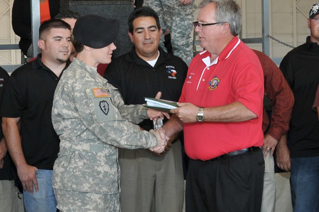 Capt. Anne McClain of the 1/14 Tomahawks of Ft. Rucker, Ala. accepts the log books to the new OH-58D Kiowa Warrior from Jim Kaylor, Corpus Christi Army Depot's Director of Aircraft Production, during a ceremony to roll out the first Kiowa Warrior returned to the fight from CCAD, Oct. 14.