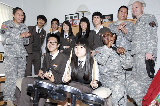 Woo Sin-bum (front left) and Ham Ji-hui (front right), 10th graders from Dongducheon Foreign Language High School, play a musical instrument computer game with American and KATUSA Soldiers Oct. 14 in a Headquarters and Headquarters Detachment, U.S. Army Garrison Casey barracks room.