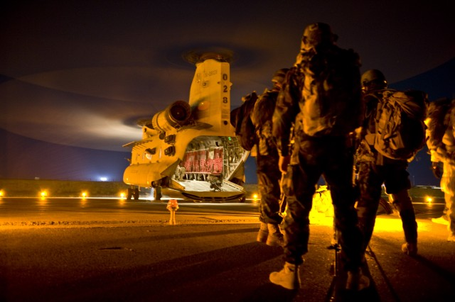 A group of Afghan Commandos with 3rd Commando Kandak, and U.S. Special Forces Soldiers with Special Operations Task Force - South, wait to board a CH-47 Chinook helicopter before an operation to rid insurgents from Panjwa'i District, Oct. 15, 2010, in Kandahar Province, Afghanistan.