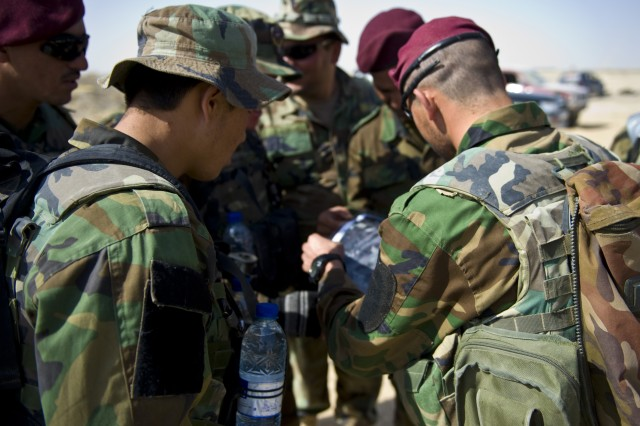 A group of Afghan Commandos, with 3rd Commando Kandak, advised by Soldiers from Special Operations Task Force - South, perform map reconnaissance during preparation for an operation to rid insurgents from Panjwa'i District, Oct. 13, 2010, in Kandahar Province, Afghanistan.
