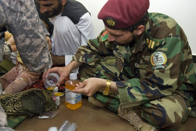 Dr. M. Haroon, with 3rd Commando Kandak based in Kandahar City, Afghanistan, mixes crushed antibiotic pills with a pediatric drink in order to hydrate 10-month-old Nawida and prevent a recurring infection Oct. 18.  Nawida underwent treatment to drain an infection from her leg.   Commandos and Soldiers from Special Operation Task Force - South, on a recent clearing operation in Kandahar Province, talked with Nawida's father and found she had an infection in her leg that was possibly life-threatening.  The partnered medical team cut open the infection and cleaned, drained and re-bandaged the wound.  Nawida was able to stand on her leg the following day.  (U.S. Army photo by Staff Sgt. Jeremy D. Crisp / Special Operations Task Force South).