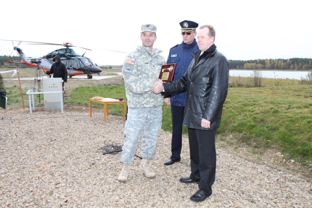 Col. John Kem, U.S. Army Corps of Engineers Europe District commander, hands over a ceremonial key plaque to members of the Estonian Police and Border Guard Bureau during a ribbon-cutting ceremony Oct. 15, 2010, officially opening a 10-by-10 meter, $240,000, illuminated helicopter landing pad in Varska, Estonia. The landing pad, funded by EUCOM and managed by USACE, will help Estonian police and border guard operate more efficiently due to the upgrades. Additionally, along with a new helicopter pad and the other upgrades north in Narva, the nearly $560,000 project includes an enclosed hanger and new surrounding pavement.
