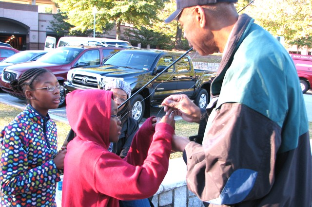 Robert Kornegay (right), shift manager at the Army and Air Force Exchange Service gas station on Fort McPherson, helps Noah Grady (center), 10, bait his hook. Noah's sister, Jovita (left), 12, and mother, Elvira (background), also attended the event. The Grady Family is enrolled in Survivor Outreach Services, a program designed to help Families of servicemembers killed in Afghanistan and Iraq.