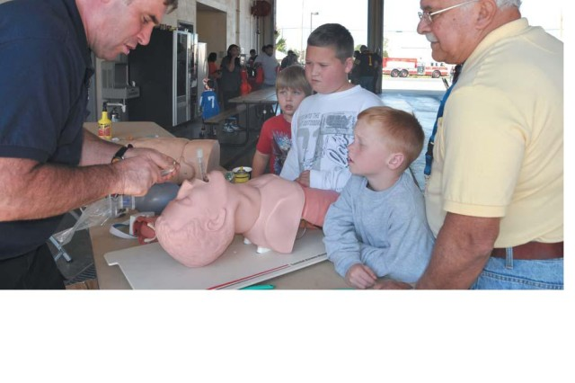 From right, Tony Saponaro, a U.S. Army Developmental Test Command contractor, his grandsons Lucas, 5, and Nicholas, 10, and Olivia Sheets, 7, watch DES emergency medical technician Scott Manglass demonstrate how to clear an airway at the lifesaving display.