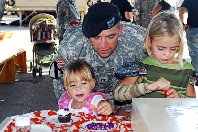 """FORT HOOD, Texas- Capt. Charles Costello, the commander of G Battery, 3rd Battalion, 82nd Field Artillery Regiment, 2nd Brigade Combat Team, 1st Cavalry Division, helps his daughters decorate cupcakes during """"Trunk or Treat"""" on Fort Hood, Texas, Oct. 19."""