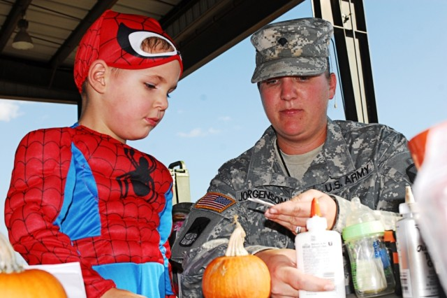 FORT HOOD, Texas- Spc. Stephanie Jorgenson, a Colorado Springs, Colo. native and a communication security specialist with 3rd Battalion, 82nd Field Artillery Regiment, 2nd Brigade Combat Team, 1st Cavalry Division, helps her son, Aries, decorate a pumpkin during the Trunk or Treat event on Fort Hood, Texas, Oct. 19.