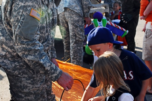 FORT HOOD, Texas- Spc. Jeff Quinn, from Portsmouth, N.H., a training room clerk for A Battery, 3rd Battalion, 82nd Field Artillery Regiment, 2nd Brigade Combat Team, 1st Cavalry Division, holds a bucket of candy while Jonathan and Lillian Phillips look through it, Oct. 19.