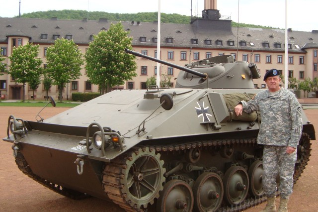 "Master Sgt. Stephen Chenault poses in front of a post-World War II ""Hotschkiss"" German Army tank used until about 1980. The tank was on display on Campbell Barracks last May. Chenault has seen 35 years of change in his career."