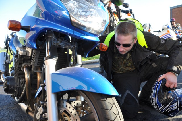 Bjoern Mosebach, a master sergeant equivalent from the German army, gives his bike a quick check at the Auto Skills Center on Chievres Air Base Oct. 21 as part of Motorcycle Safety Awareness Day.