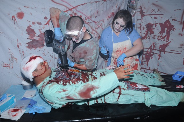Pfc. Justin Eisenhauer and volunteer Brandy Sarver operate on Spc. Jan Kongsy in the Better Opportunities for Single Soldiers haunted house autopsy room last year. For more information on this year's post Halloween events, visit www.ftruckermwr.com.